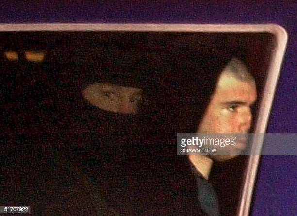 Taliban fighter John Walker Lindh rides in the back seat with a security officer 23 January 2002 as they arrive at the Alexandria Detention Center in...