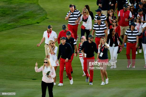 Team along with wives and girlfriends move enmass to the trophy presentation during the Sunday singles matches at the Presidents Cup at Liberty...