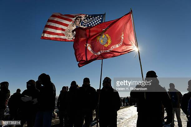 USveterans and native americans hold flags in solidarity on the road near Oceti Sakowin Camp on the edge of the Standing Rock Sioux Reservation on...