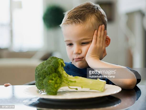 USA, Utah, Alpine, boy (6-7) resting cheek on hand by plate of broccoli