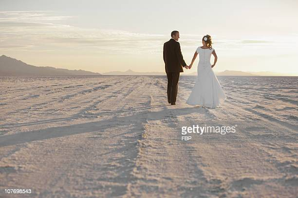 USA, Utah, Boneville Salt Flats, Bride and groom holding hands in desert