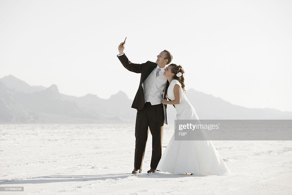 USA, Utah, Boneville Salt Flats, Bride and groom photographing themselves in desert : Stock Photo