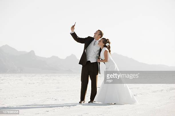 usa, utah, boneville salt flats, bride and groom photographing themselves in desert - utah wedding stock pictures, royalty-free photos & images