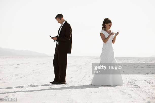 usa, utah, boneville salt flats, bride and groom texting in desert - utah wedding stock pictures, royalty-free photos & images