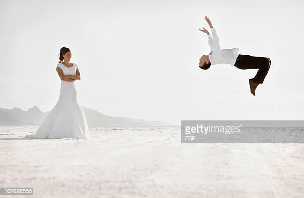 usa, utah, boneville salt flats, bride watching groom performing backflip in desert - utah wedding stock pictures, royalty-free photos & images