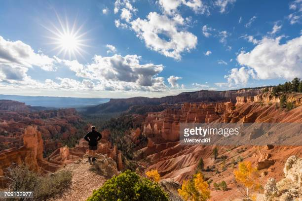 USA, Utah, Bryce Canyon National Park, tourist looking at hoodoos in amphitheater at Rim Trail