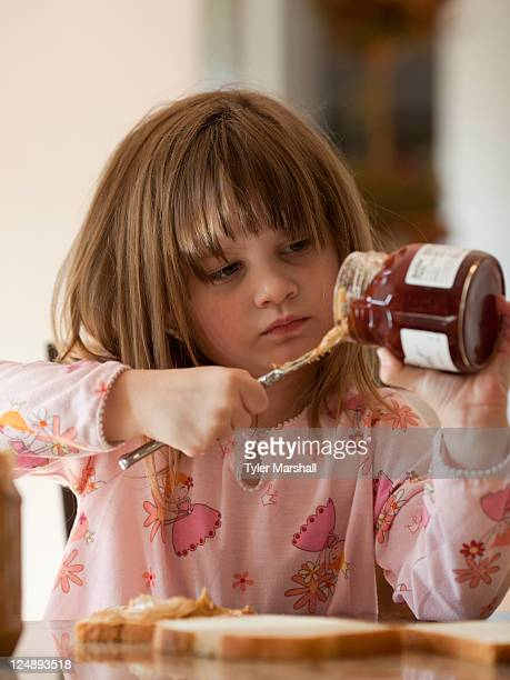 USA, Utah, Cedar Hills, Girl (4-5) putting jam on bread
