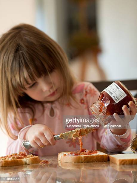 USA, Utah, Cedar Hills, Girl (4-5) spreading jam on bread