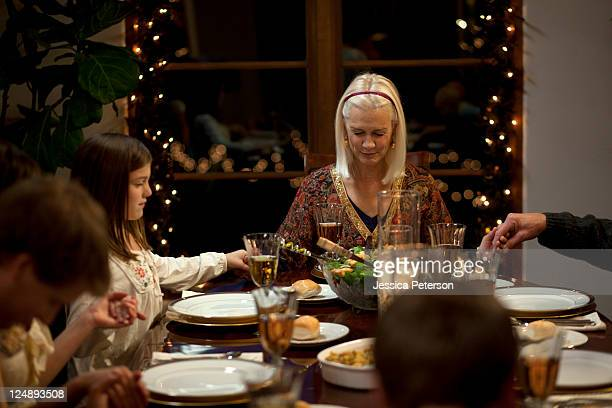 USA, Utah, Cedar Hills, Three generation family with girl (8-9) holding hands at Christmas table
