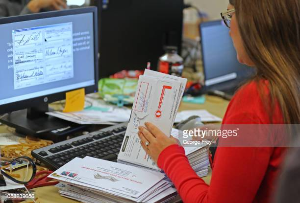 Utah County election worker verifies signatures on mail-in ballots for the midterm elections on November 6, 2018 in Provo, Utah. Utah early voting...