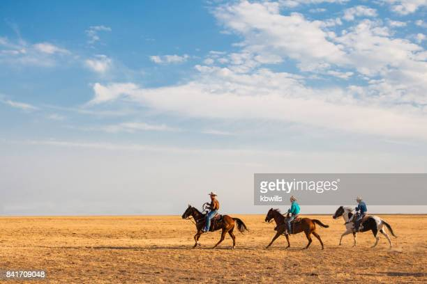 utah cowboys in distance riding with stetson, shirt and using  lasso
