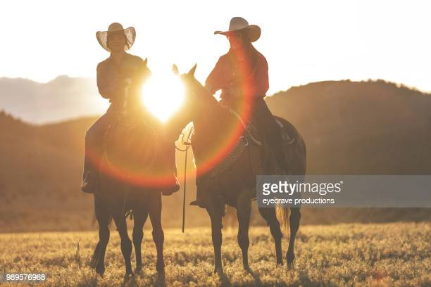 utah cowgirls at sunset western outdoors and rodeo stampede roundup riding horses herding livestock - artemisia stock pictures, royalty-free photos & images