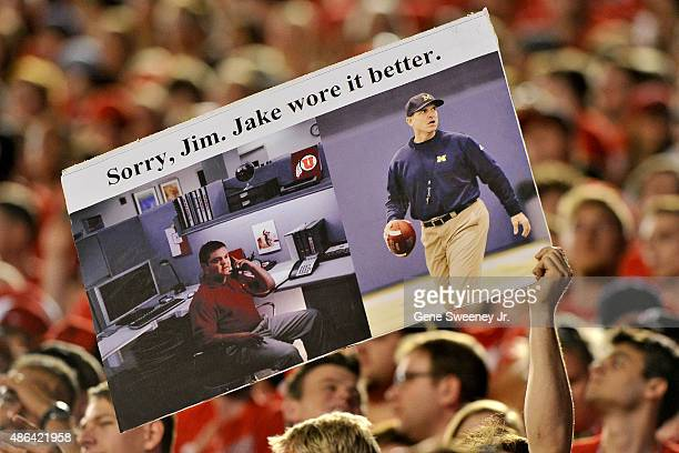 """Utah fans hold up a sign making fun of head coach Jim Harbaugh of the Michigan Wolverines love of Khaki pants, comparing him to """"Jake of State Farm""""..."""