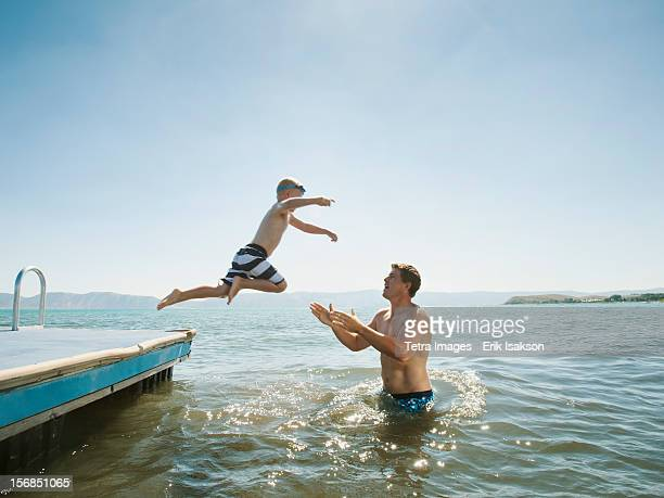 usa, utah, garden city, boy (4-5) jumping into lake caught by his father - standing water stock pictures, royalty-free photos & images