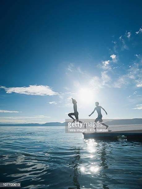 USA, Utah, Garden City, Boys (10-11,12-13) jumping from raft
