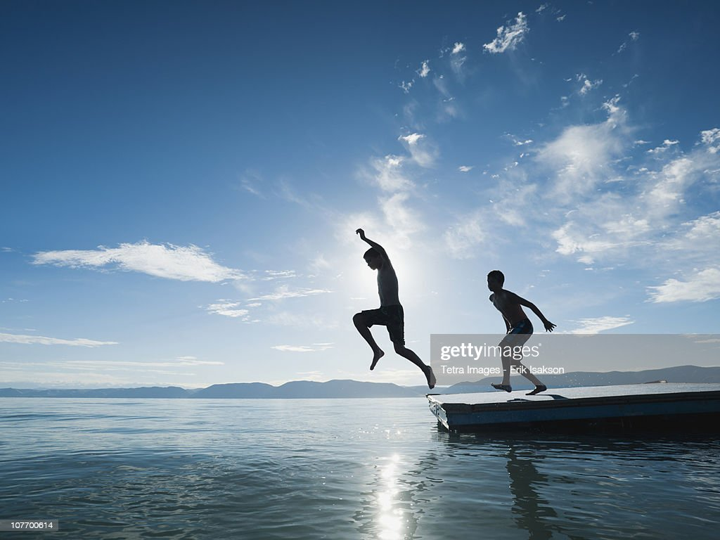 USA, Utah, Garden City, Boys (10-11,12-13) jumping from raft : Stock Photo
