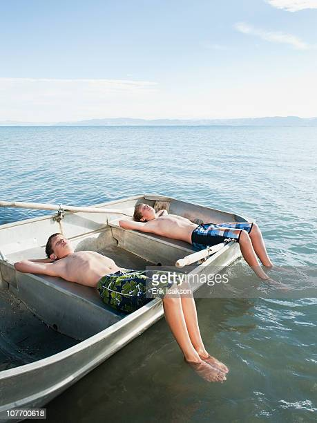 USA, Utah, Garden City, Boys (10-11,12-13) resting on boat