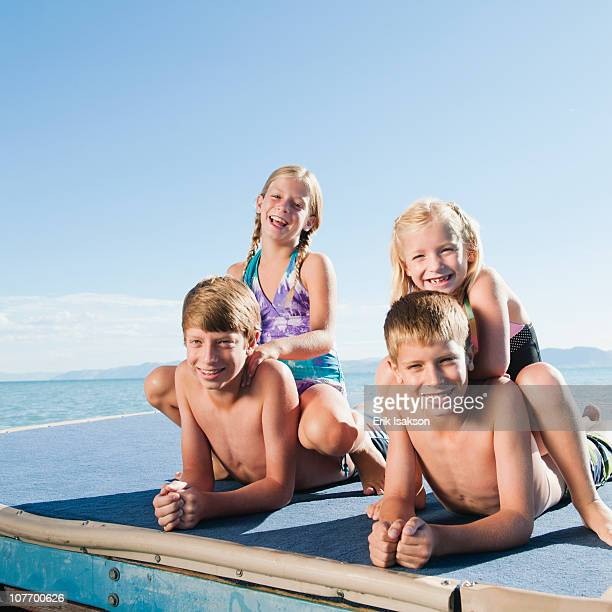 USA, Utah, Garden City, Kids (6-7,8-9,10-11,12-13) playing on raft on lake