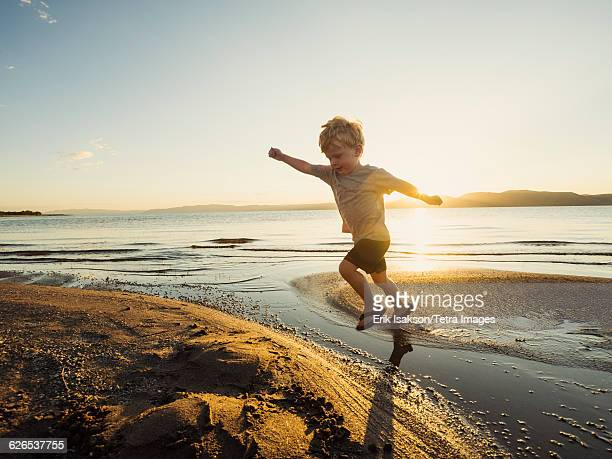usa, utah, garden city, small boy (4-5) jumping over water on sunny day - sandy utah stock pictures, royalty-free photos & images