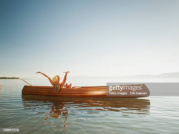 usa, utah, garden city, young woman relaxing in canoe with arms raised - standing water stock pictures, royalty-free photos & images