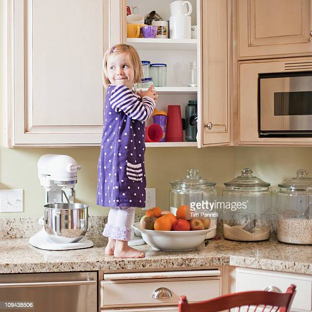 usa, utah, girl (2-3) climbing on cupboard in kitchen - verboten stock-fotos und bilder