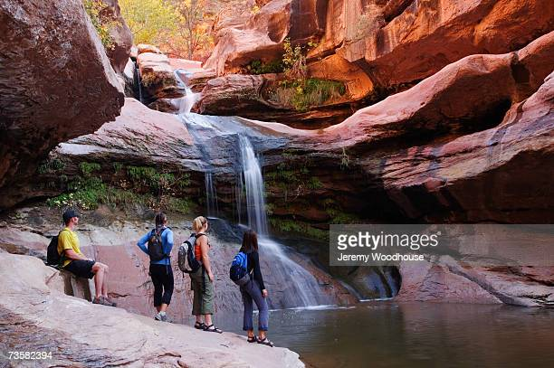 USA, Utah, group of hikers at canyon waterfall