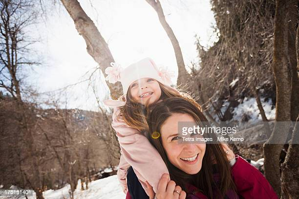 USA, Utah, Highland, Young woman carrying her daughter (2-3) on shoulders
