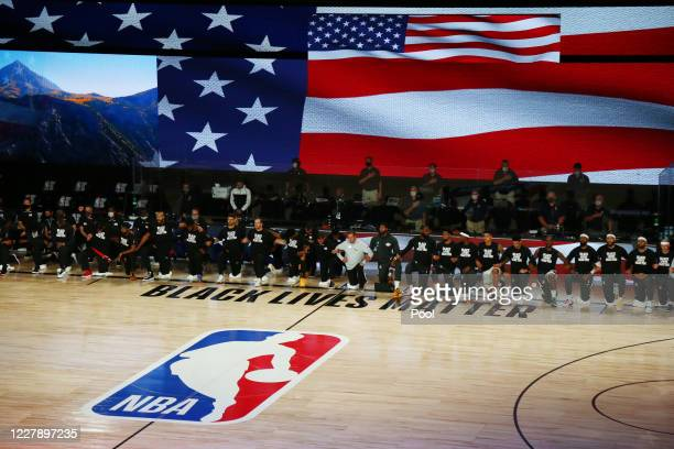 Utah Jazz and Los Angeles Lakers players and staff kneel during the National Anthem before an NBA game at The Arena at ESPN Wide World Of Sports...