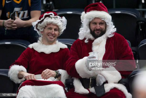 Utah Jazz fans Jordan Robison Santa and Jay Bass Mrs Claus watch the pregame warmups before the Utah Jazz game against the Portland Trail Blazers at...
