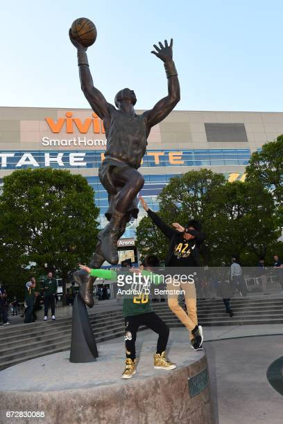 Utah Jazz fans pose for a photo with the statue of Karl Malone outside vivint.SmartHome Arena before Game Three of the Western Conference...