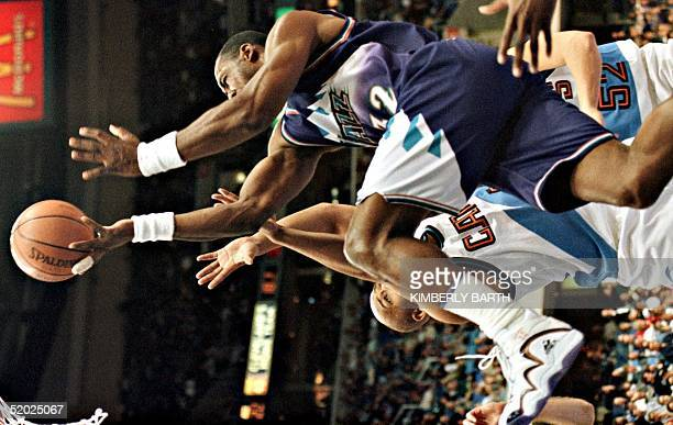 Utah Jazz forward Karl Malone puts up two points over Cleveland Cavaliers center Shawnelle Scott in the first half of their game 21 December at Gund...