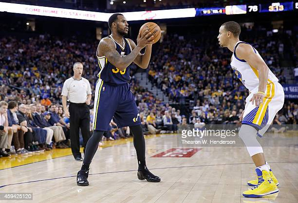 Utah Jazz forward Trevor Booker looks to pass the ball over Golden State Warriors guard Stephen Curry at ORACLE Arena on November 21 2014 in Oakland...
