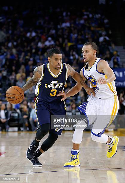 Utah Jazz guard Trey Burke dribbles the ball while guarded by Golden State Warriors guard Stephen Curry at ORACLE Arena on November 21 2014 in...