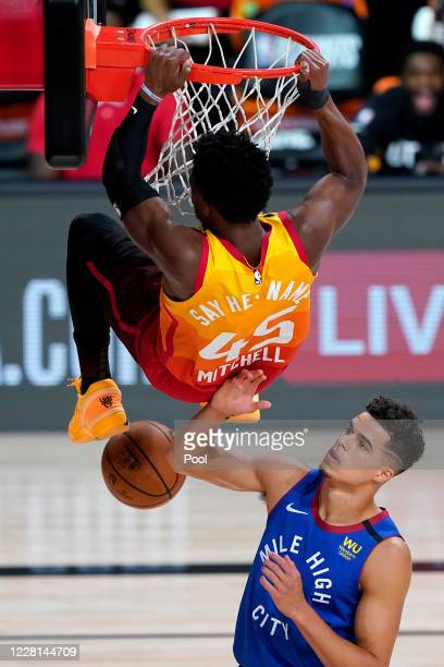 Utah Jazz's Donovan Mitchell dunks over Denver Nuggets' Michael Porter Jr. During the first half of an NBA basketball first round playoff game at...