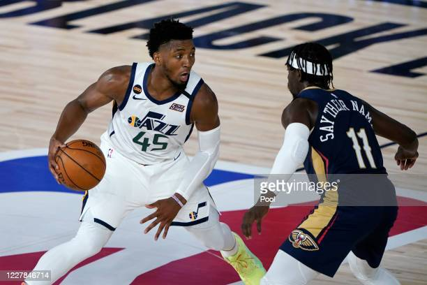Utah Jazz's Donovan Mitchell heads to the basket past New Orleans Pelicans' Jrue Holiday during the second half of an NBA basketball game on July 30,...