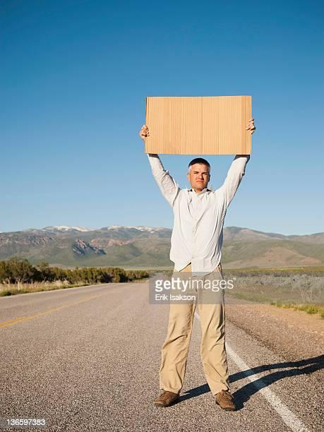USA, Utah, Kanosh, Mid-adult man hitch-hiking in barren scenery