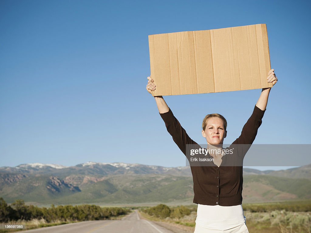 USA, Utah, Kanosh, Mid-adult woman hitch-hiking in barren scenery : Stock Photo