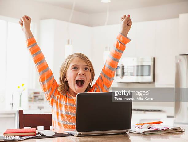 USA, Utah, Lehi, Excited girl (6-7) with laptop