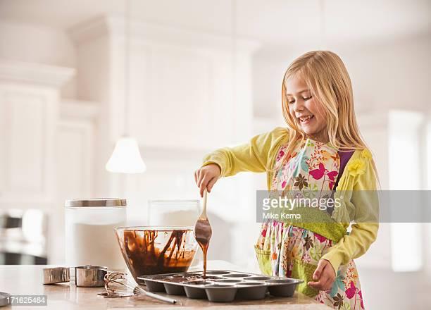 USA, Utah, Lehi, Girl (6-7) baking cupcakes