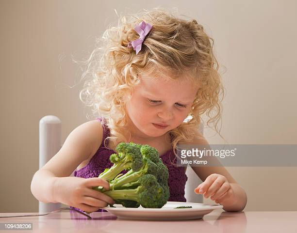 USA, Utah, Lehi, girl (2-3) eating broccoli