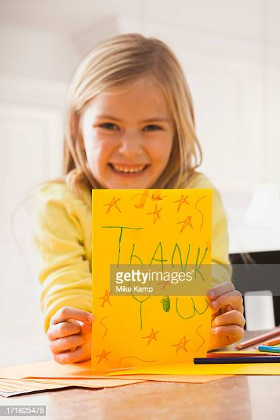 USA, Utah, Lehi, Girl (6-7) holding drawing with text 'thank you'