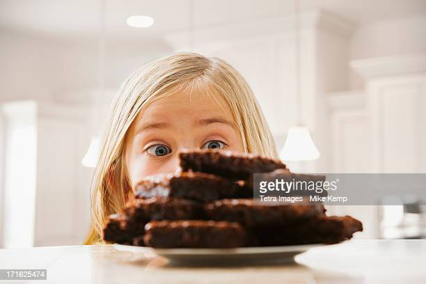 USA, Utah, Lehi, Girl (6-7) looking at heap of brownies
