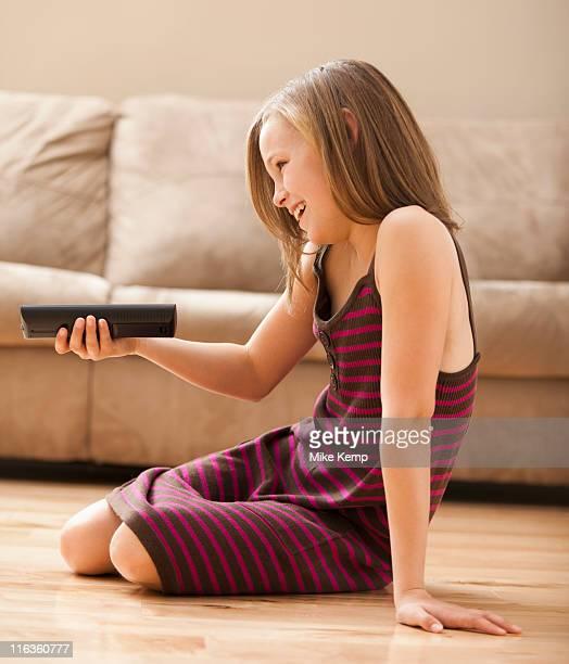 USA, Utah, Lehi, Girl (10-11) sitting on floor, watching TV