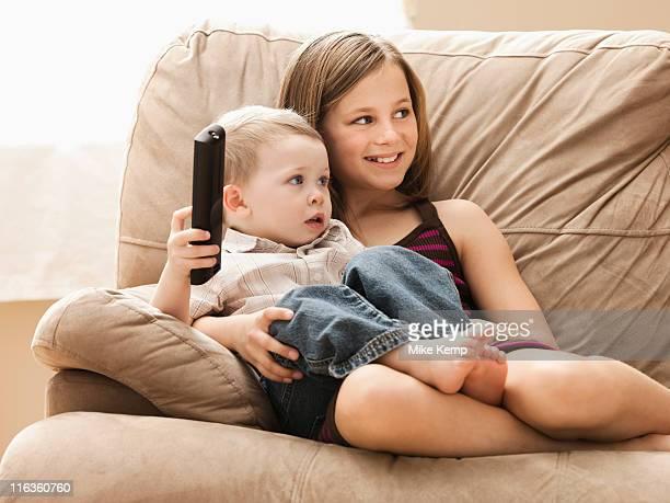 USA, Utah, Lehi, Girl (10-11) with brother (2-3) sitting on sofa, watching TV