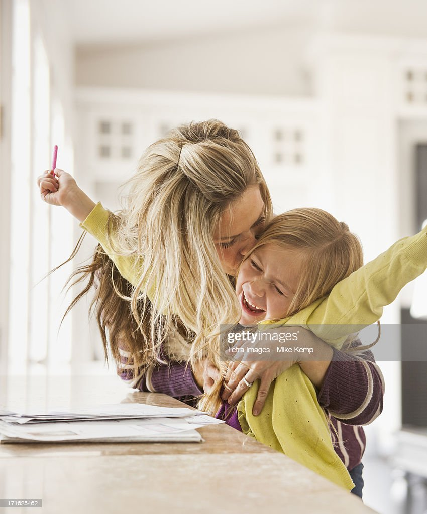 USA, Utah, Lehi, Mother kissing daughter (6-7) during doing homework : Stock Photo