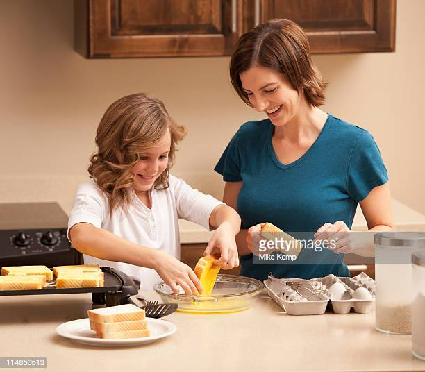 USA, Utah, Lehi, Mother preparing breakfast with daughter (10-11) in kitchen