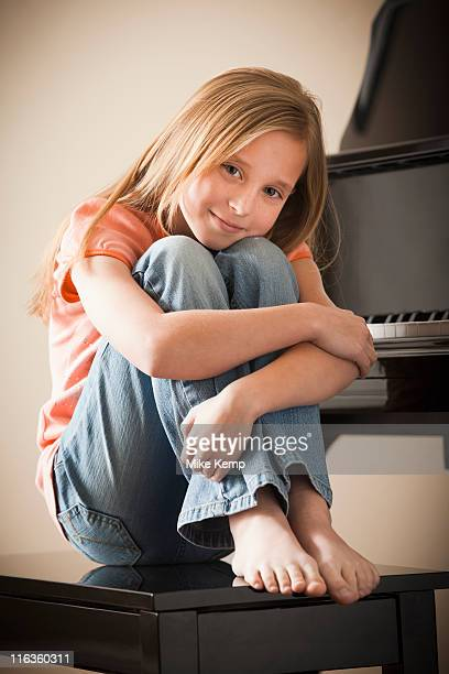 USA, Utah, Lehi, Portrait of girl (8-9) sitting by piano