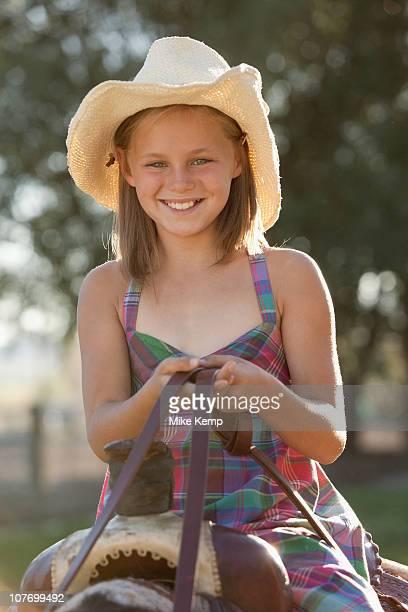 USA, Utah, Lehi, Portrait of smiling cowgirl (8-9) horseback riding in ranch