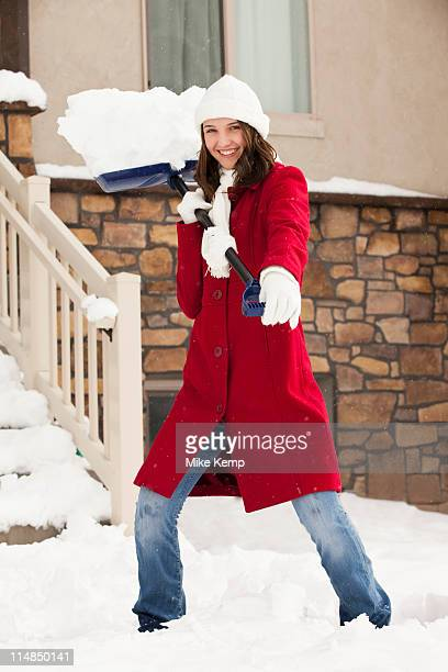 USA, Utah, Lehi, Portrait of young woman throwing snow using snow shovel