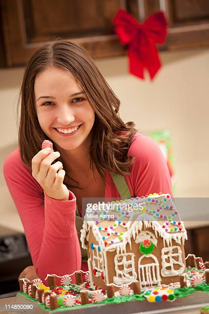 USA, Utah, Lehi, Portrait of young woman with gingerbread house in kitchen